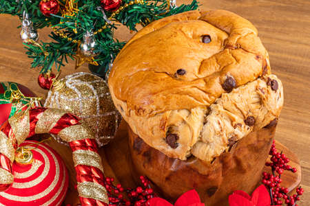 Panettone with chocolate on wooden table, traditional Italian dessert cake for Christmas. Top view.