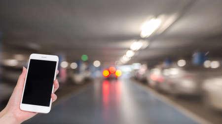 屋内駐車場をぼかした背景とボケ味の光、社会的ネットワーク、インターネットの構築と携帯電話を持つ手 写真素材
