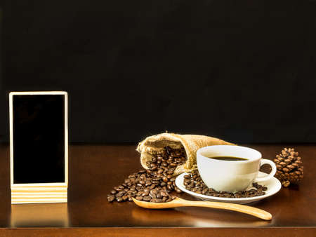 White cup coffee with coffee beans and blank chalk board on wooden top table