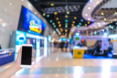 Hand holding mobile phone with indoor cars exhibition show blurred background and bokeh light, Social network, internet