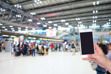 空港ターミナル付きの携帯電話を手に持ち、背景に旅行者の群衆をぼかし、ボケライト、ソーシャルネットワーク、インターネット、旅行コンセプ