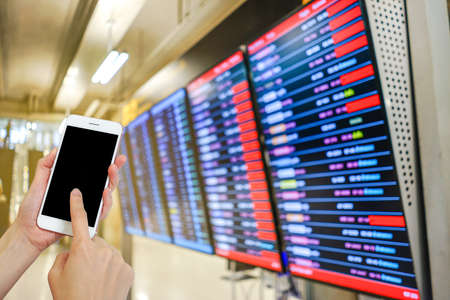 Hand holding mobile phone with airport terminal blurred crowd of Travelling people on the background, Bokeh light, Social network, internet,Traveling concept Stock Photo