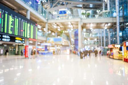 空港ターミナルは、背景にボケの光を持つ旅行者の群衆をぼかしました。旅行のコンセプト。