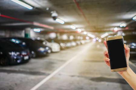 屋内駐車場エリア、インターネット、ソーシャルメディアのぼやけた画像を持つ携帯電話を手持ち