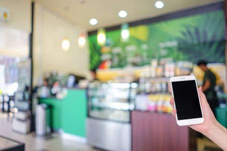 背景の使用、ボケライト、ソーシャルネットワーク、インターネットのためのぼやけたコーヒーカフェと携帯電話を手持ち