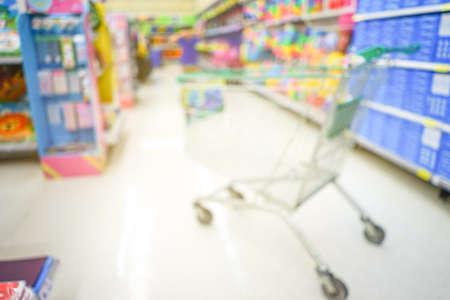 空のショッピングカートぼやけた背景を持つスーパーマーケットの通路 写真素材