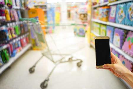 ショッピングモールで手持ち携帯電話ぼかし背景とボケ光、インターネット、ソーシャルメダイ 写真素材