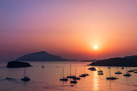Next to the Temple of poseidon in Greece there is a marina of boats. Thos photo was taken at that spot at sunset. The fog on the horizon line created light spreading causing a very warm atmosphere. In the foreground it is possible to see multiple sail boats