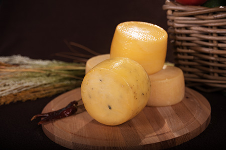 Various yellow cheeses on the dark board