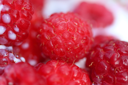 A background of ripe red raspberry with milk Фото со стока