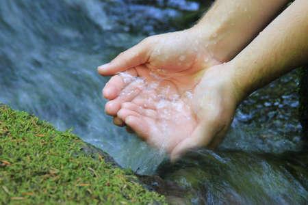 Un par de manos ahuecando el agua de un manantial puro de la montaña Foto de archivo