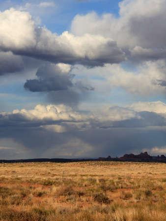 Distant clouds promise rain to desert landscape