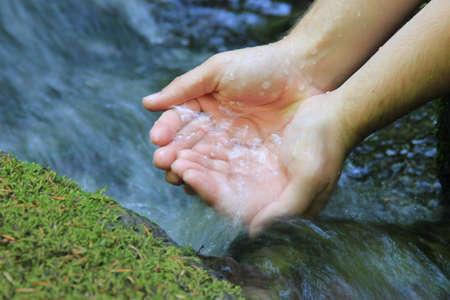 source d eau: Une paire de mains ventouses eau d'une source pure de la montagne Banque d'images