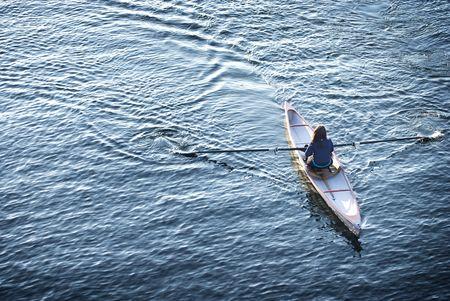 Jonge vrouw in een rij-boot omringd door water