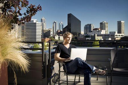 Jonge man met behulp van laptop op een stedelijke dak dek.