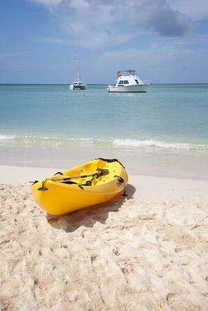 Gele kajak op het strand met boten op de achtergrond Stockfoto