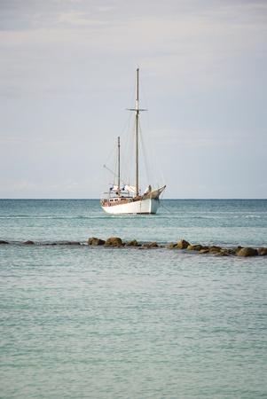 Sailboat Anchored Off Shore in the Caribbean Stockfoto