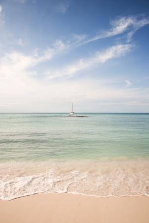 Strand en lucht in het Caribisch gebied met zeilboot verankerd in de verte