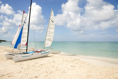 hobie: Hobie catamaran sailboats pulled up onto the beach Stock Photo