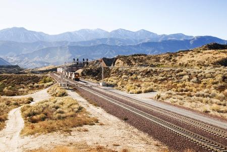 Trein in de verte bewegen langs sporen in de Amerikaanse woestijn
