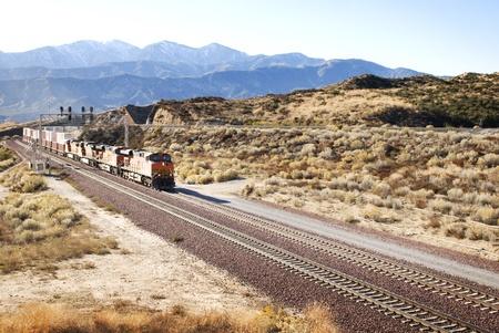 Train bewegen langs sporen in de Amerikaanse woestijn