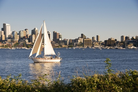 Sailboat on a lake in with a city skyline in the background photo