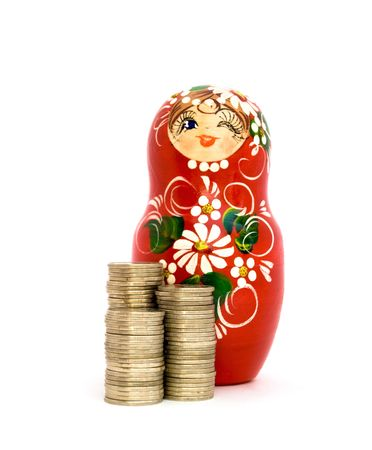 matroshka: Russian doll and piles of russian roubles coins isolated on white. Stock Photo