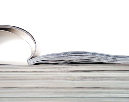 Stack of magazines with opened one on white background.