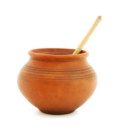 crock: Clay pot with wooden spoon on white background Stock Photo