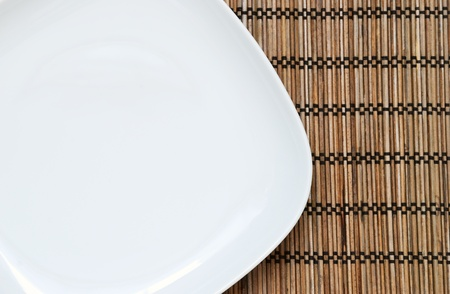 Empty plate on the bamboo napkin, top view photo