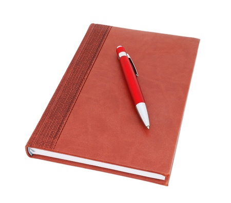 Leather notebook with red ballpoint pen isolated on white background photo