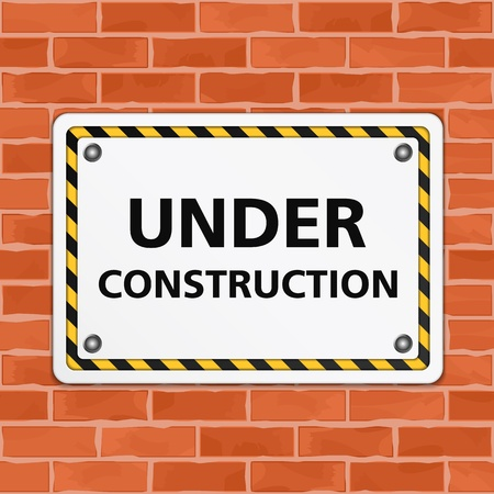 building bricks: Under construction sign on brick wall