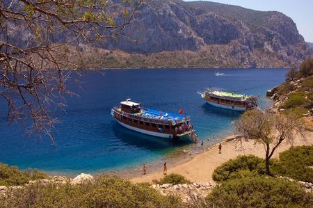 moored: Turkish cruise boats moored near an island in Aegean sea.