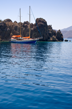 A lonely yacht moored near a rocky island in Aegean sea. Stock Photo