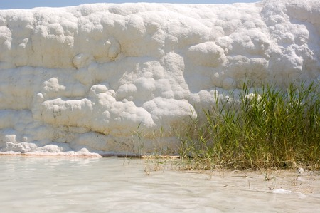 A natural purely white wall of calcium in Pamukkale, a natural site and attraction in south-western Turkey. natural phenomenon of thick white layers of limestone and travertine cascading down the mountain slope resembling a frozen waterfall.