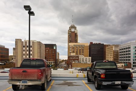 Two trucks staying on the top of a parking lot. A view of Lansing downtown, Michigan, USA.