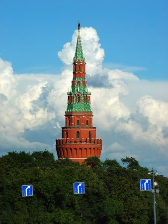 The Kremlin tower in Moscow, Russia with a nice cloudscape in the background. 3 road signs in the lower part of the shot.