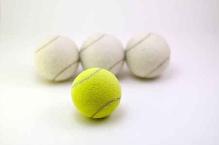 White tennis balls with yellow ball ion front. Stock Photo