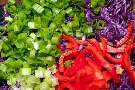 Picado ingredientes de la ensalada. Cebollas, pimientos, lombarda.