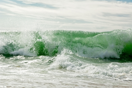 A wave breaks at the ocean shore
