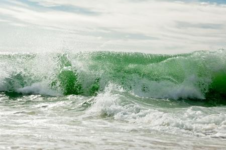 Een golf breekt op de oceaan kust