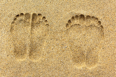 Two pairs of foot prints on the sand photo