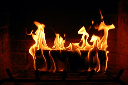 Burning fire log lighting the fireplace and heating a house Foto de archivo
