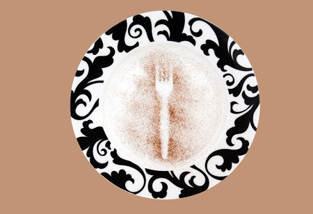 Fork imprint on the plate, with ground cinnamon around  Isolated plate on the beige background  Studio shot, no reflections on the plate