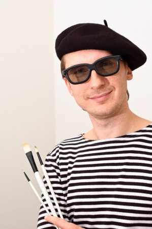French artist in beret with three brushes
