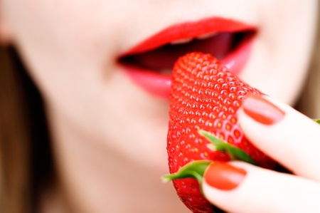 Biting a fresh bright strawberry, variations of red color, shallow depth of field Stock Photo