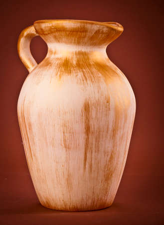 Old ceramic jug on brown  background photo