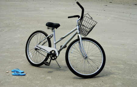 beach cruiser: A pair of flip flops on the ebacj next to a bicycle