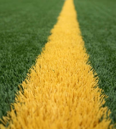Close up of yellow goal line on a green american football field