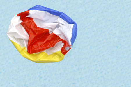 A deflated beach ball floating in a swimming pool symbolizing the end of summer.